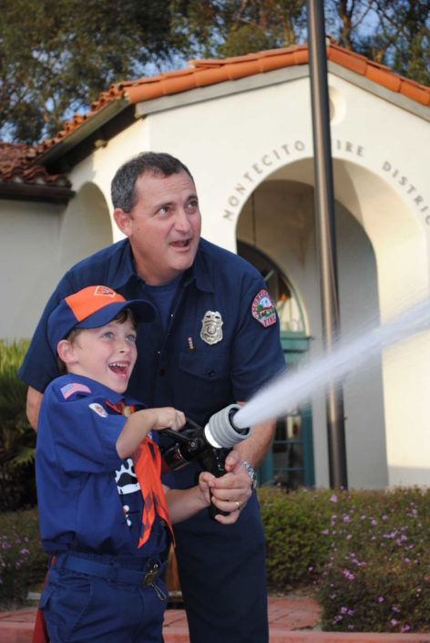 Montecito firefighter with child running fire hose