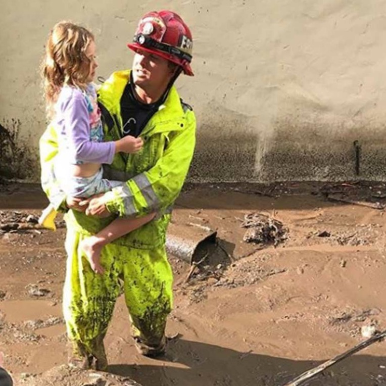 firefighter holding little girl in mudslide