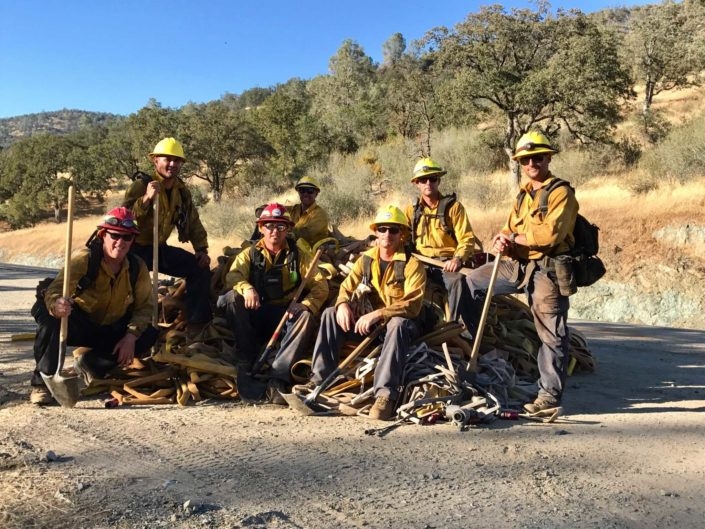 Montecito firefighters posing with axes, shovels, hose